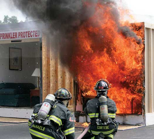 Firefighters battle a blaze in an unsprinklered room during one of HFSC's fire and sprinkler burn demonstrations.