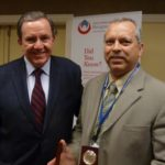 "NFPA President Jim Shannon (left) awards NIFSAB Executive Director Tom Lia with the ""Home Fire Sprinkler Champion"" award."